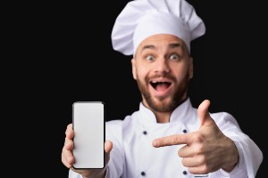 Male chef showing how to video a cooking class on his cell phone