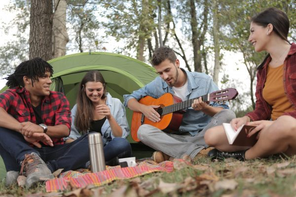 Four young adults playing guitar at over nighttcampsite